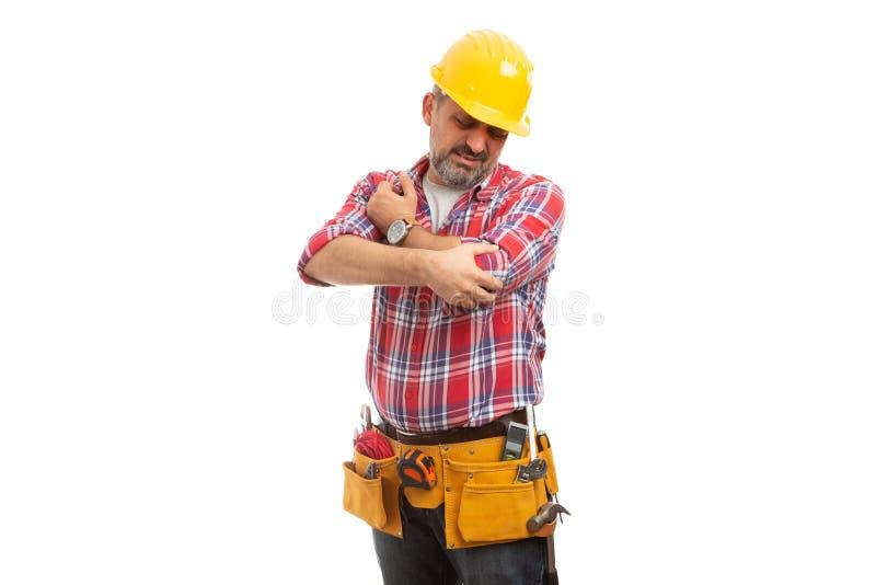 Trabajador de construcción que mira el codo imagenes de archivo