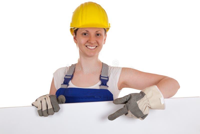 Trabajador de construcción que muestra en una muestra blanca imagen de archivo