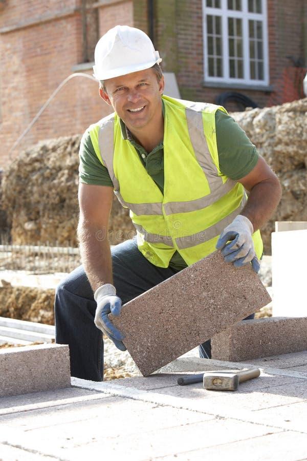 Trabajador de construcción que pone el perpiaño imagenes de archivo