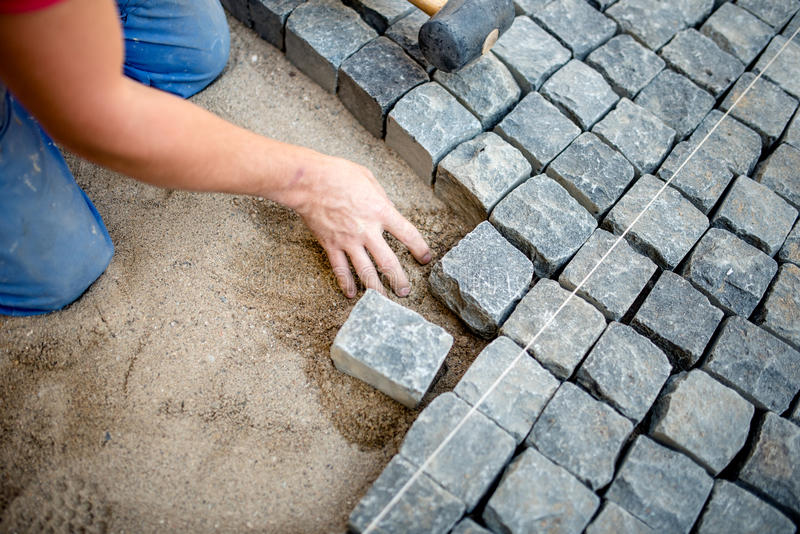 Trabajador de construcción que pone los guijarros y los bloques de la piedra en el pavimento imágenes de archivo libres de regalías