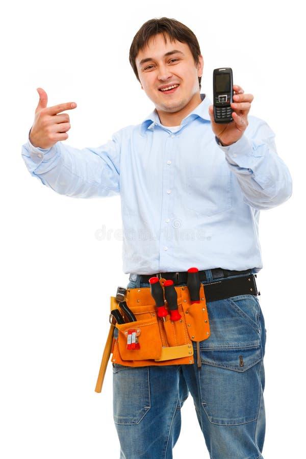 Trabajador de construcción que señala en móvil fotos de archivo libres de regalías