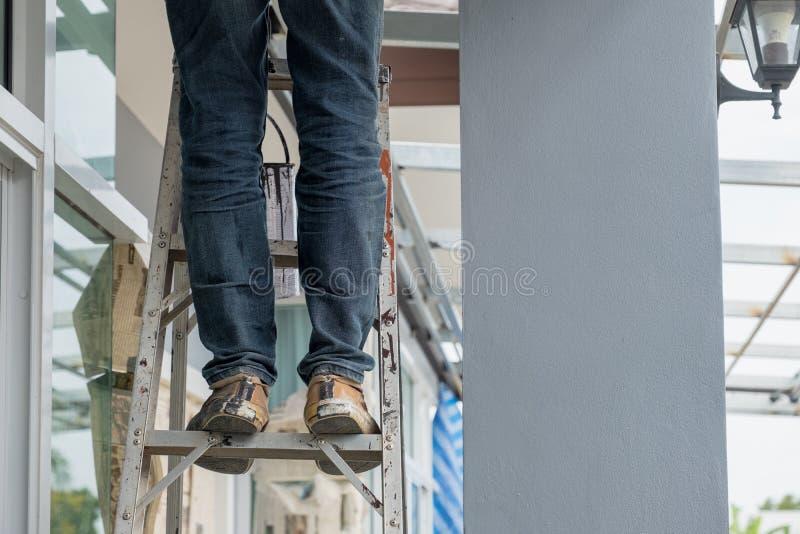 Trabajador de construcción que se coloca en las escaleras de aluminio fotografía de archivo