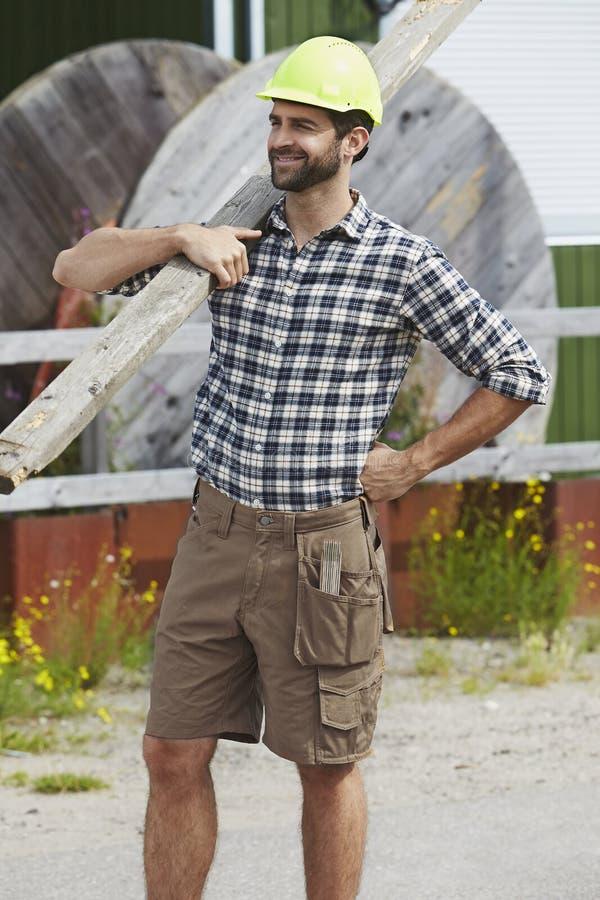 Trabajador de construcción que sostiene el tablón fotografía de archivo