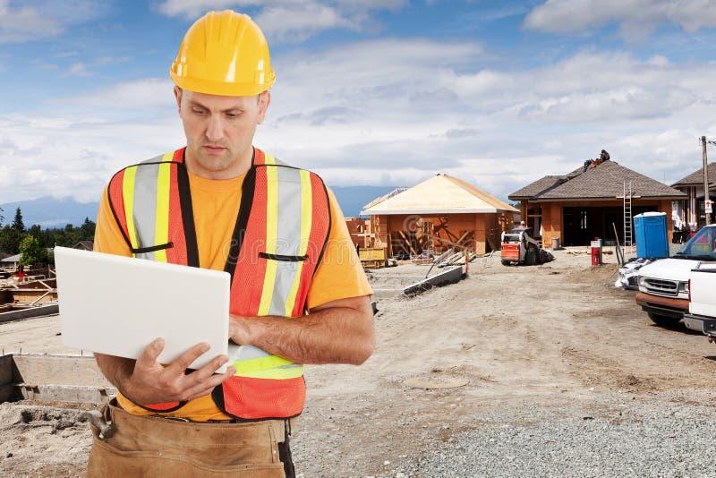 Trabajador de construcción que usa el ordenador en emplazamiento de la obra imagen de archivo libre de regalías