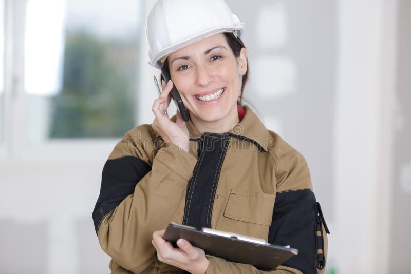 Trabajador de construcción de sexo femenino que habla en el teléfono móvil fotografía de archivo libre de regalías