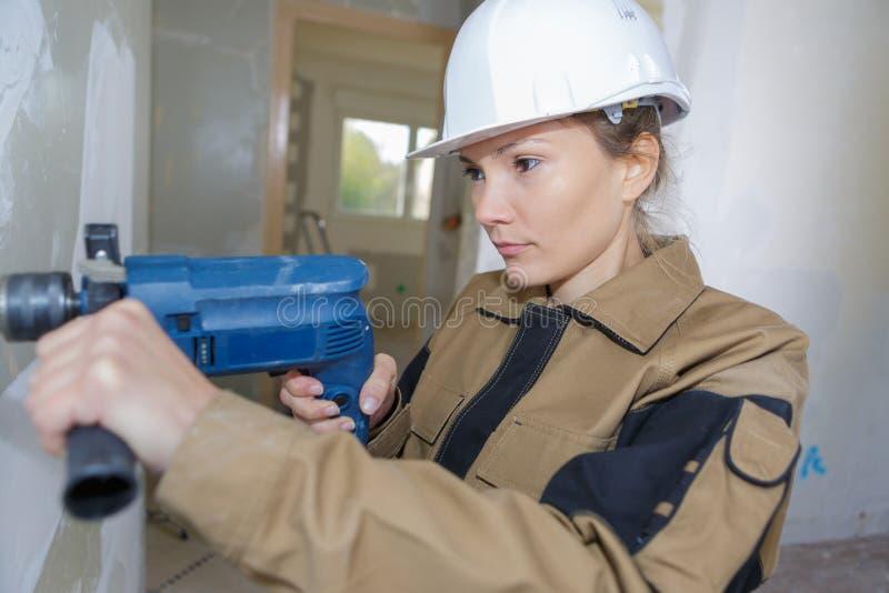 Trabajador de construcción de sexo femenino que perfora wal concreto imagen de archivo libre de regalías