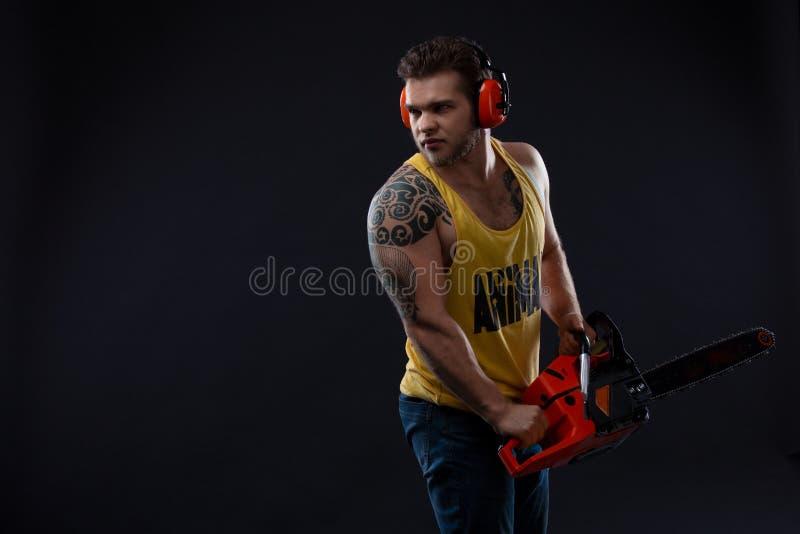Trabajador de construcción de sexo masculino con la motosierra Retrato de un hombre muscular fuerte Constructor hermoso joven Var fotografía de archivo