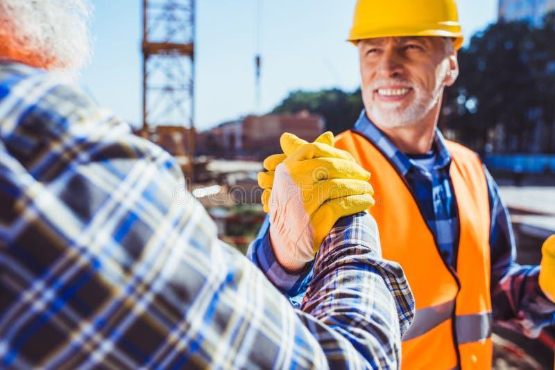 Trabajador de construcción sonriente en el uniforme protector que sacude las manos foto de archivo libre de regalías