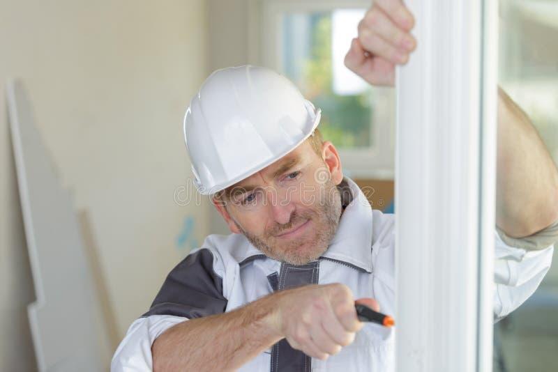Trabajador de construcci?n Installing New Windows en casa imagen de archivo