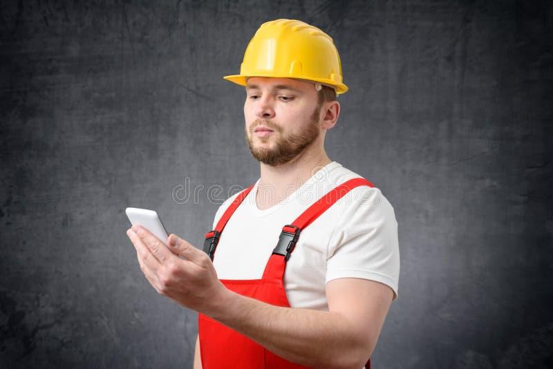 Trabajador de construcci?n que usa smartphone imagen de archivo libre de regalías