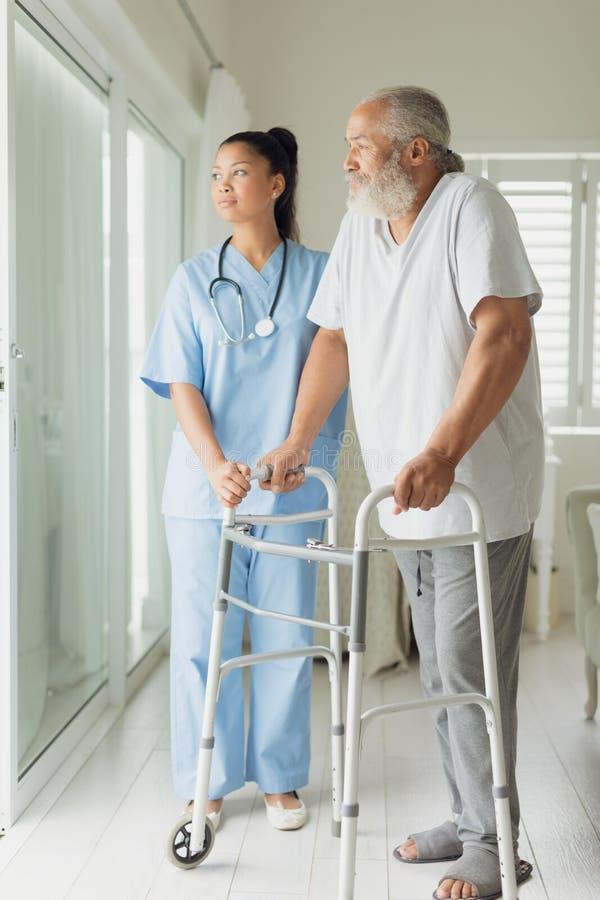 Trabajador de la atención sanitaria con el hombre usando ayuda que camina fotografía de archivo libre de regalías