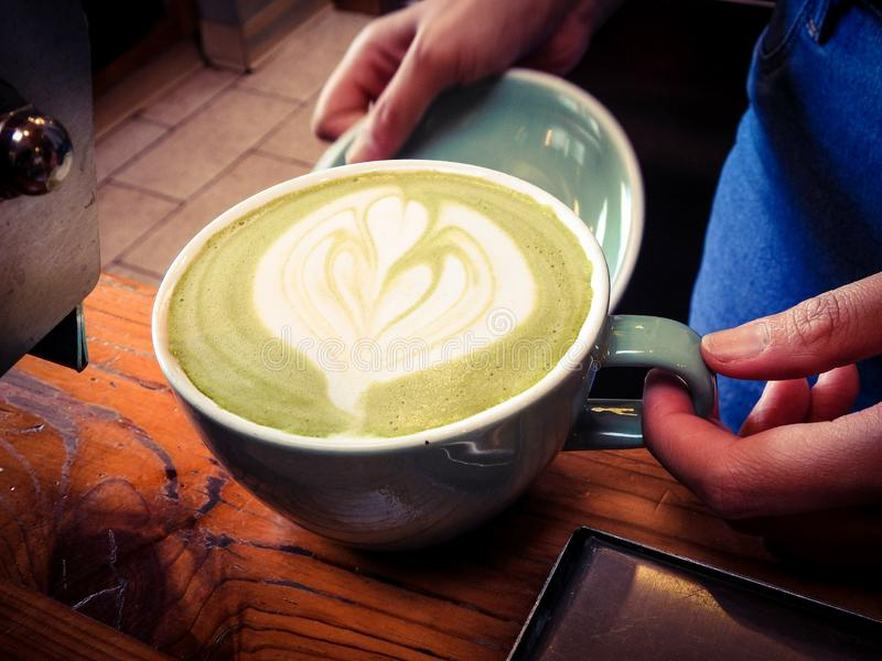 Trabajador de la cafetería que prepara un Latte del té verde de la moca fotografía de archivo libre de regalías