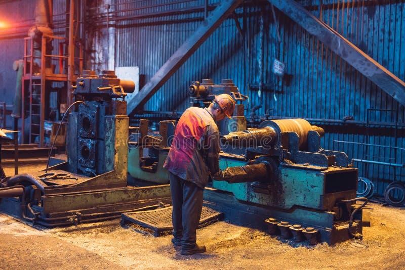 Trabajador de la industria pesada que trabaja difícilmente en la máquina Ambiente industrial áspero fotografía de archivo
