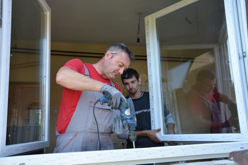 Trabajador de la instalación de Windows con un taladro fotos de archivo libres de regalías