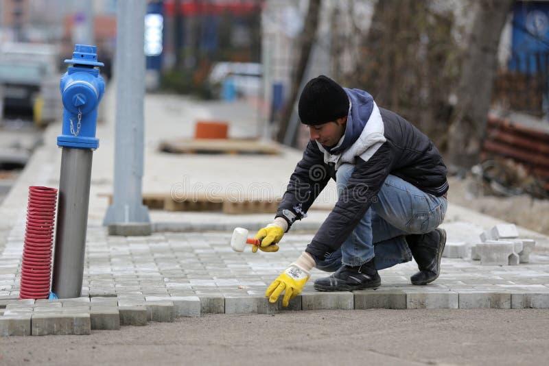 Trabajador de la piedra de pavimentación imagenes de archivo