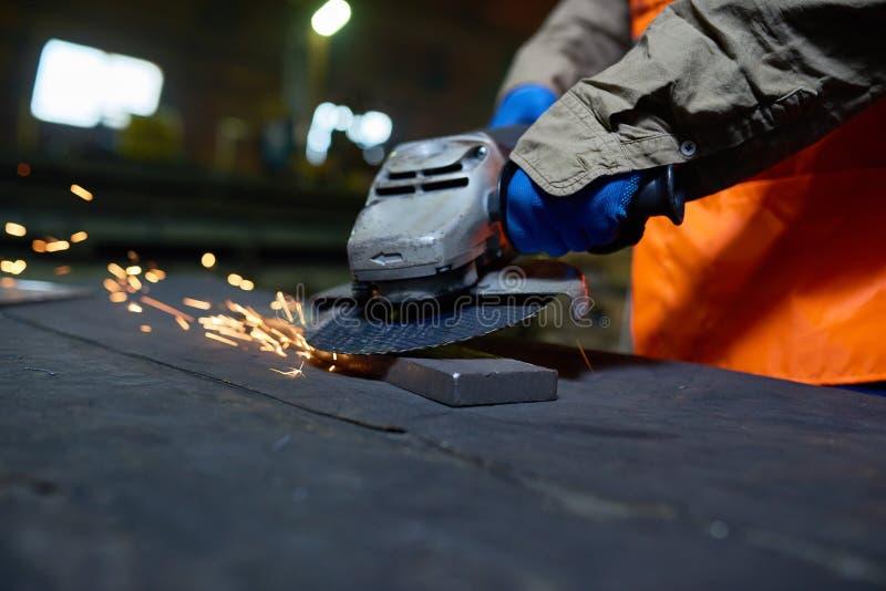 Trabajador de la planta siderúrgica que usa la amoladora de ángulo foto de archivo