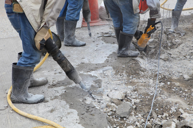 Trabajador de la tierra del cemento de la perforación de la construcción de carreteras fotografía de archivo