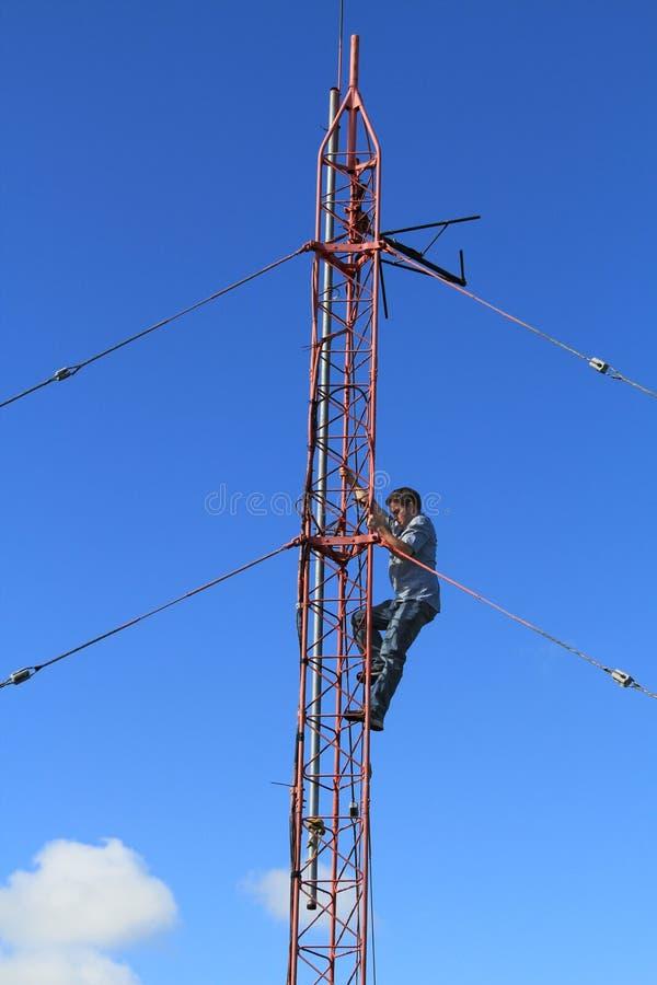 Trabajador de la torre de radio que sube en una torre fotos de archivo