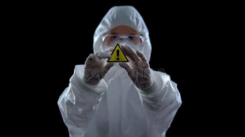 Trabajador de laboratorio con traje que sostiene un símbolo de precaución genérico en las manos, fondo negro fotos de archivo