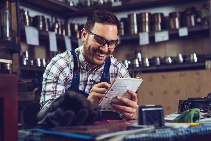 Trabajador de las instalaciones del almacenamiento de la metalurgia que hace inventario pedido fotografía de archivo