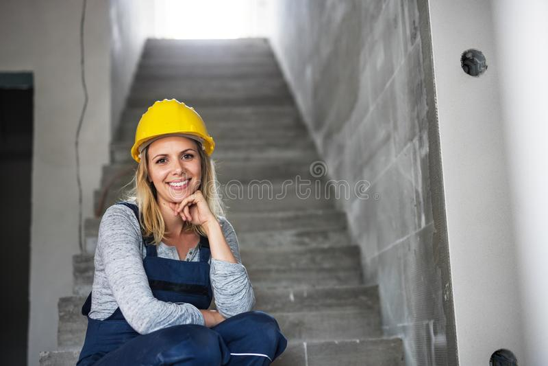 Trabajador de mujer joven con un casco amarillo que se sienta en las escaleras en el emplazamiento de la obra imagen de archivo