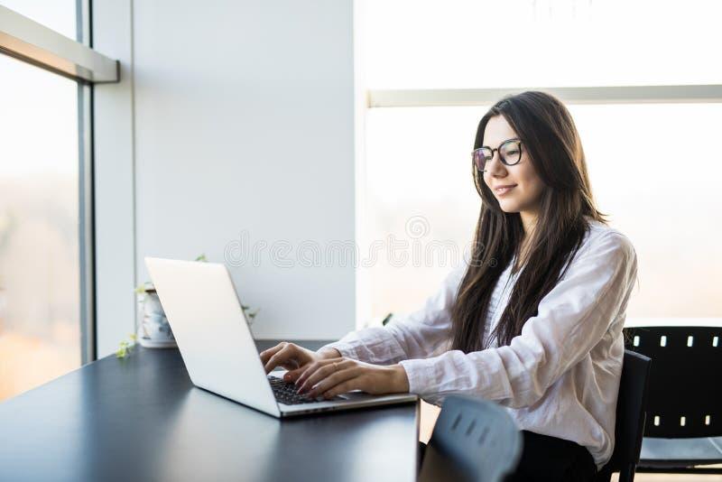 Trabajador de mujer que se sienta en oficina mientras que usa el ordenador portátil y mecanografía por el teclado imagen de archivo