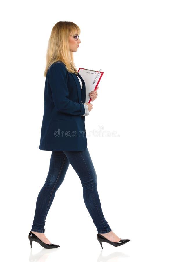 Trabajador De Office En Serio Camina Con El Portapapeles foto de archivo
