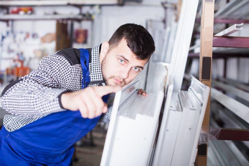 Trabajador de producción con las ventanas del PVC foto de archivo
