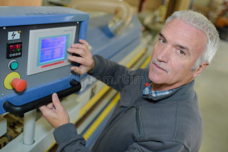 Trabajador de producción que maneja los dispositivos desprendibles en fábrica fotografía de archivo