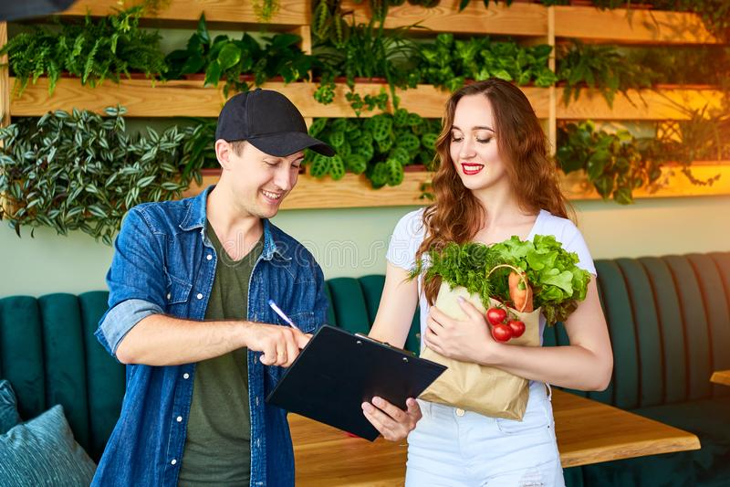 Trabajador de servicio de comida entregando comida fresca, entregando bolso de compra a una feliz clienta en la cocina en casa Co imagen de archivo libre de regalías