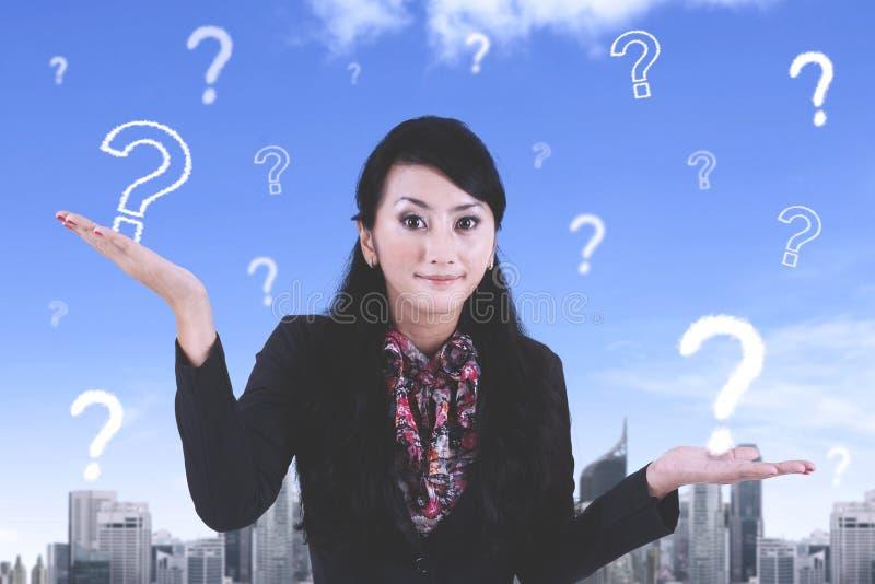 Trabajador de sexo femenino confuso con los signos de interrogación imagenes de archivo