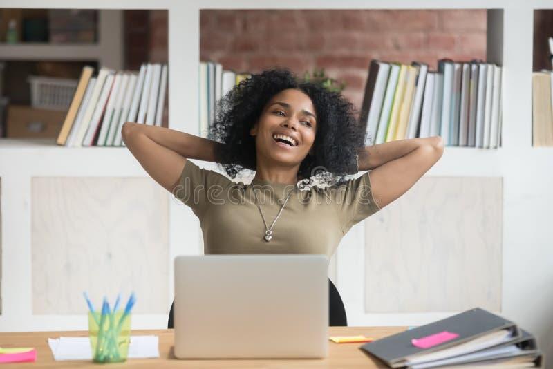 Trabajador de sexo femenino del afroamericano relajado feliz satisfecho con el trabajo acabado foto de archivo