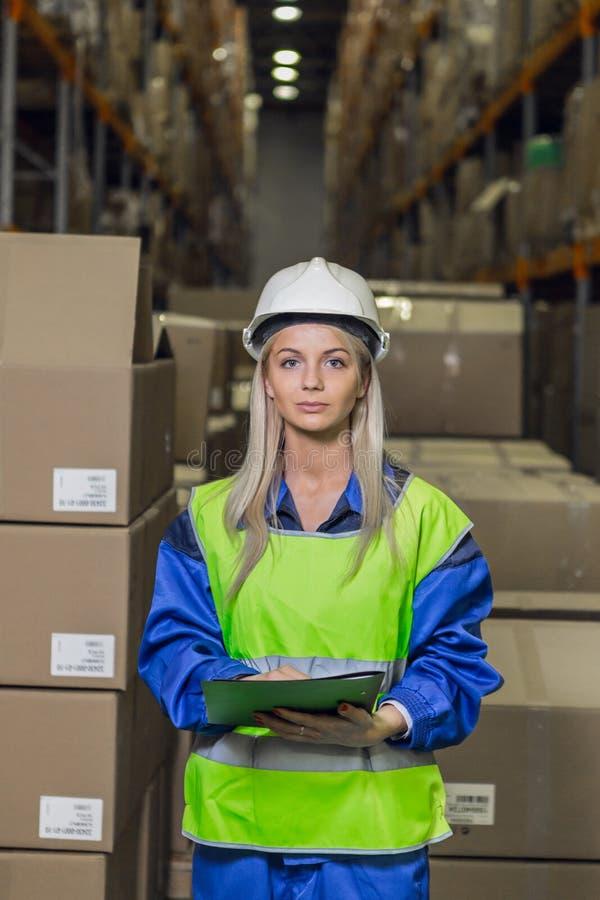 Trabajador de sexo femenino del almacén que mira la cámara fotos de archivo libres de regalías