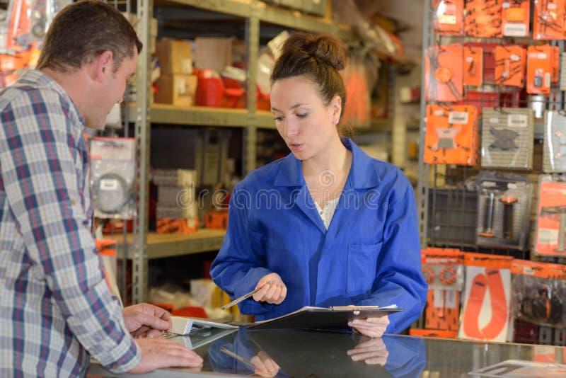 Trabajador de sexo femenino en el cliente assiting contrario del almacén fotos de archivo