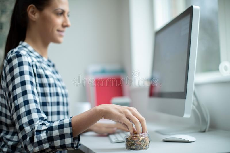 Trabajador de sexo femenino en la oficina que come el bocado sano de nueces y de semillas secadas foto de archivo