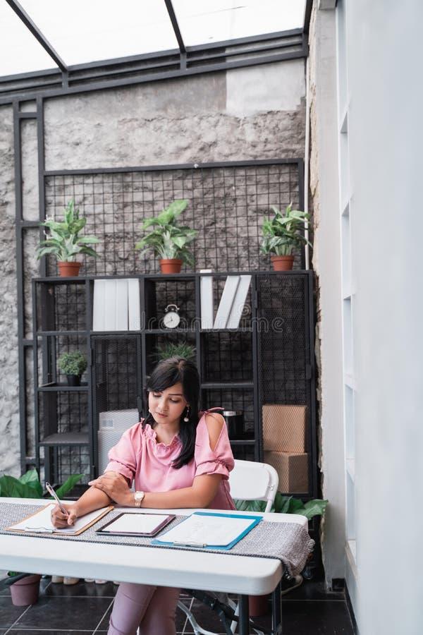 Trabajador de sexo femenino en su oficina que trabaja en papeleo imágenes de archivo libres de regalías