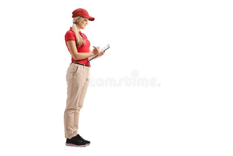 Trabajador de sexo femenino en un uniforme que escribe en un tablero fotos de archivo libres de regalías
