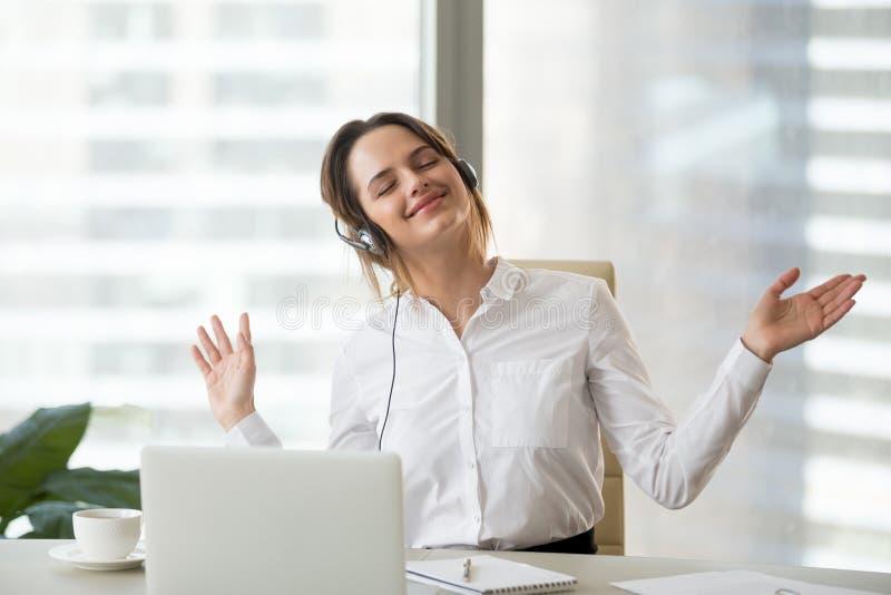 Trabajador de sexo femenino feliz que disfruta de música preferida en el trabajo imagenes de archivo