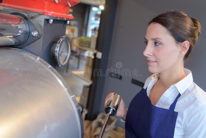 Trabajador de sexo femenino joven cerca del tanque en fábrica de la cervecería de la cerveza foto de archivo libre de regalías