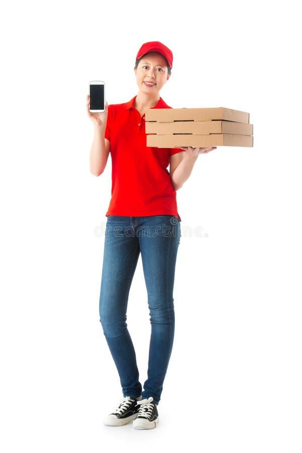 Trabajador de sexo femenino joven hermoso de la entrega que sostiene la caja imagen de archivo