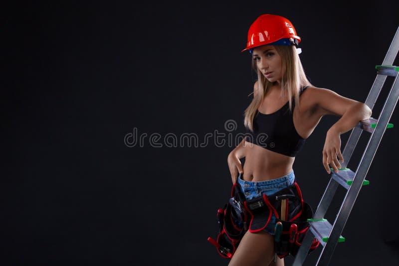 Trabajador de sexo femenino de la construcción atractiva con la escalera en fondo negro la mujer está llevando un casco de la con fotografía de archivo