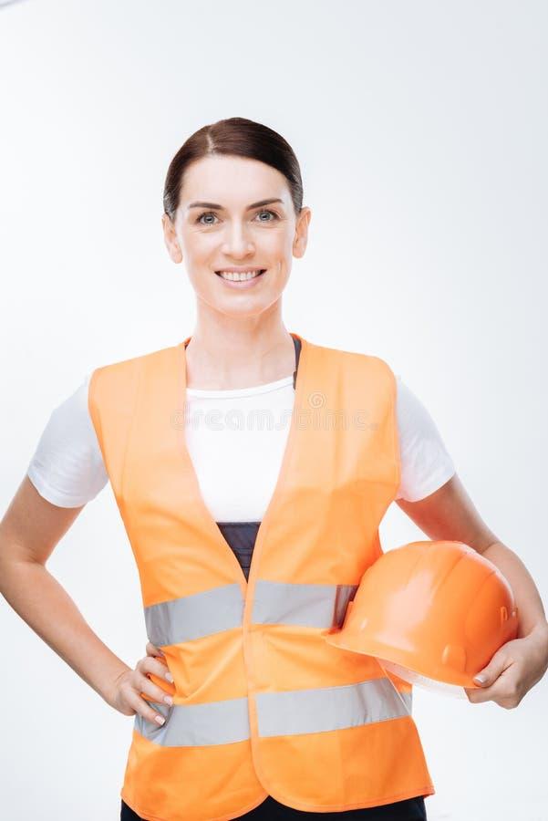 Trabajador de sexo femenino moreno que sostiene el casco fotografía de archivo