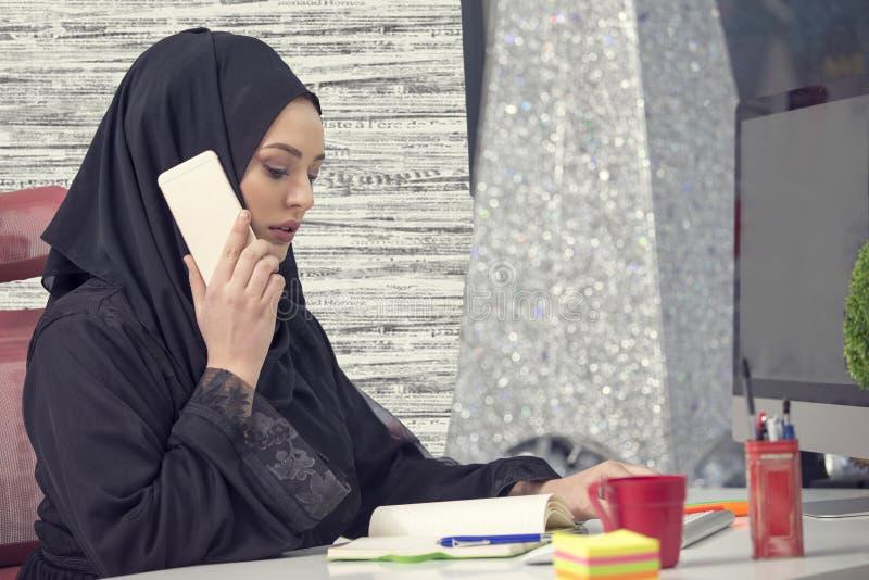 Trabajador de sexo femenino musulmán que habla en el teléfono mientras que trabaja con el ordenador portátil foto de archivo libre de regalías