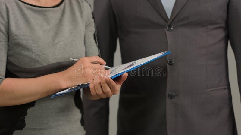 Trabajador de sexo femenino que hace notas en la carta financiera, encontrando con el jefe masculino, informe imagen de archivo