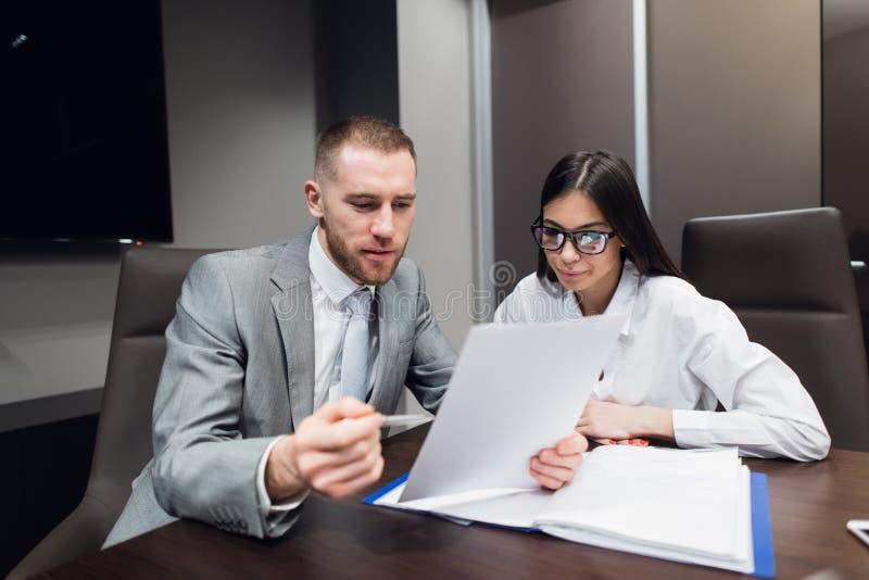 Trabajador de sexo femenino que muestra los papeles a su jefe serio en la sala de reunión fotografía de archivo libre de regalías