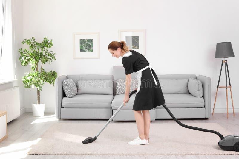 Trabajador de sexo femenino que quita la suciedad de la alfombra con el aspirador profesional, dentro imagenes de archivo