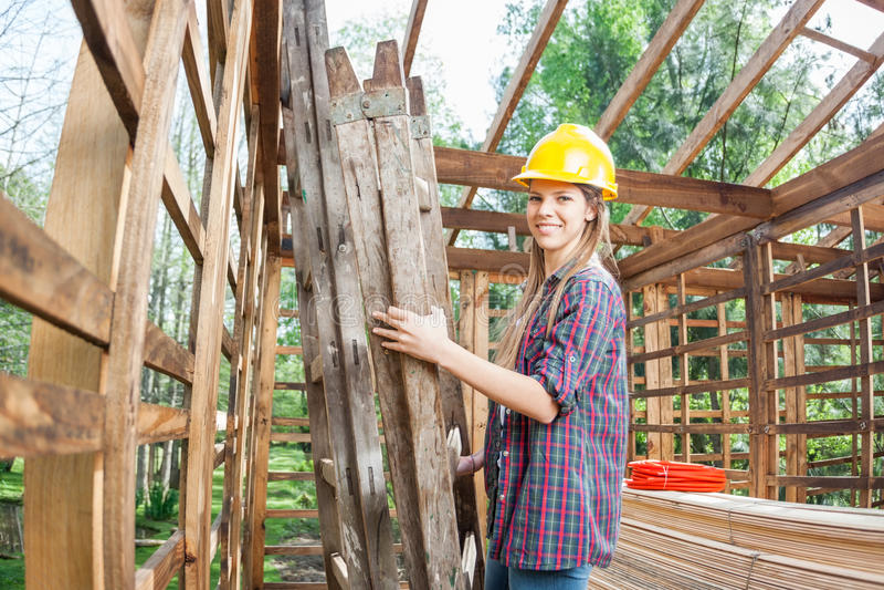 Trabajador de sexo femenino que sostiene la escalera en cabina de madera en imagen de archivo