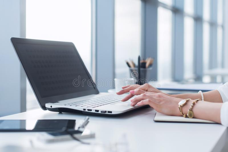 Trabajador de sexo femenino que usa el ordenador portátil en la oficina, trabajando con nuevo proyecto Mujer blogging en casa com imagen de archivo libre de regalías