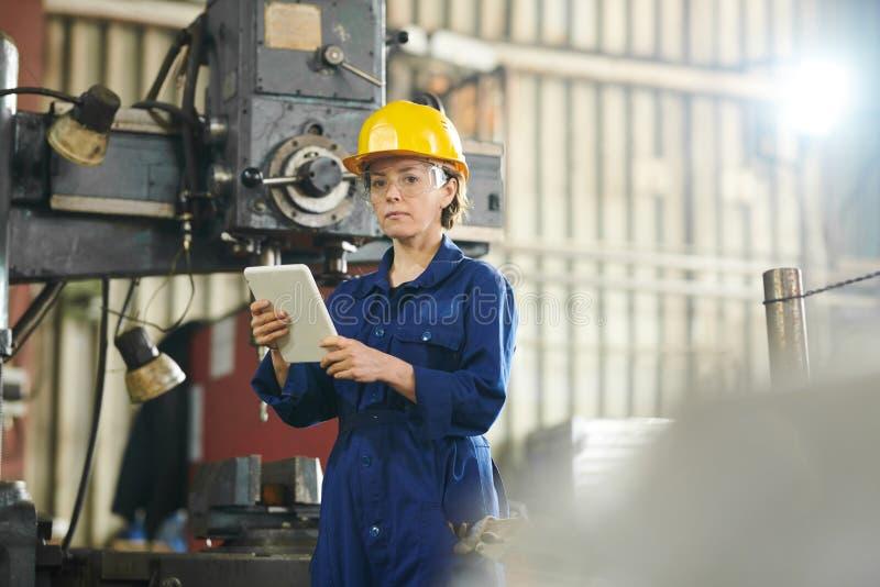 Trabajador de sexo femenino usando la tableta en la fábrica imagen de archivo