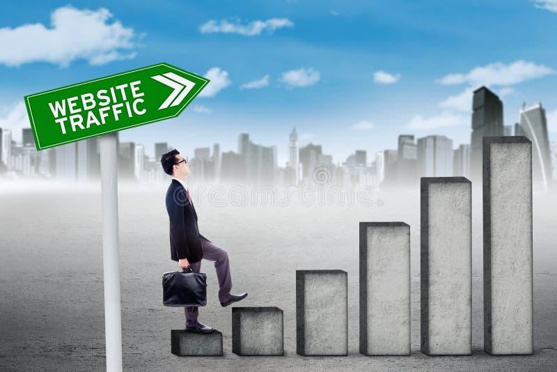 Trabajador de sexo masculino con el gráfico del tráfico del sitio web fotos de archivo libres de regalías